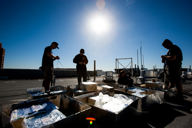 Pyrotechnicians, from left, Joseph Rubio, Christopher Murray, Sandy Fahey and Anthony Kappel of Fireworks by Grucci twist wires to hook up to multi-shot boxes in preparation of the New Year's Eve  ...