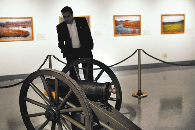 Governor Brian Sandoval checks out the original Fremont Cannon exhibit at the Nevada State Museum in Carson City on Oct. 25, 2013. The photos on the wall show locations where John C. Fremont and h ...