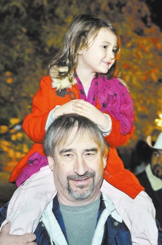 Edan Bitsko watches the Christmas parade from atop her grandfather Randy Bitsko's shoulders during WinterFest in the Water Street District in Henderson on Saturday, Dec. 14, 2013. (Bill Hughes/Las ...