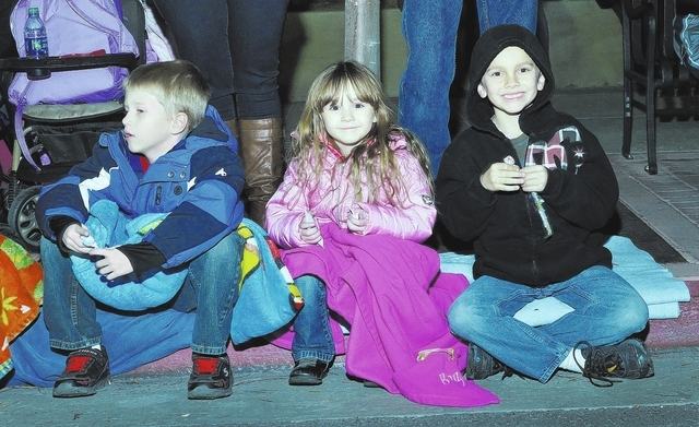 Hayden Mauro, left, his sister Brayah, center, and Liam Buist watch as the Christmas parade passes by during WinterFest in the Water Street District in Henderson on Saturday, Dec. 14, 2013. (Bill  ...