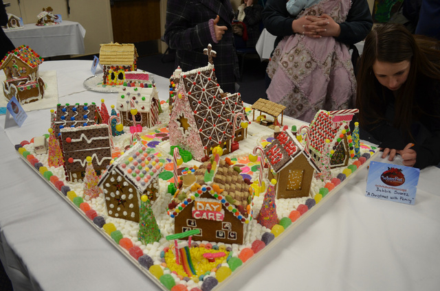 """Visitor fill out ballots to vote for gingerbread house competition entries such as Bobbie Suarez's """"A Christmas With Family"""" at Henderson WinterFest, Dec. 14, 2013. (Ginger Meurer/Las Ve ..."""