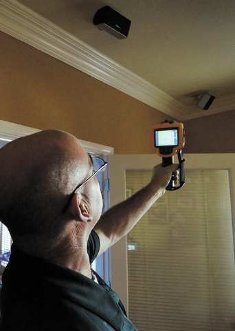 Bill Douglas, a project manager with Today's Energy Store, uses a thermal imaging unit to check for air leaks and substandard or missing insulation while doing a home energy assessment at a house  ...