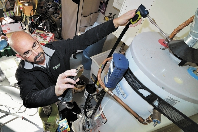 Bill Douglas, a project manager with Today's Energy Store, checks a water heater while doing a home energy assessment at a house near the intersection of Viento Del Montagna Avenue Cabana Blanca S ...