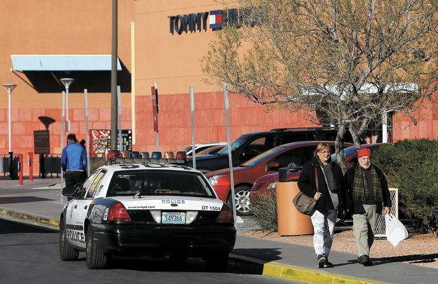 Consumers walk past a police car while shopping at the Las Vegas Premium Outlets mall near downtown Las Vegas on Dec. 10, 2013. (Jason Bean/Las Vegas Review-Journal)