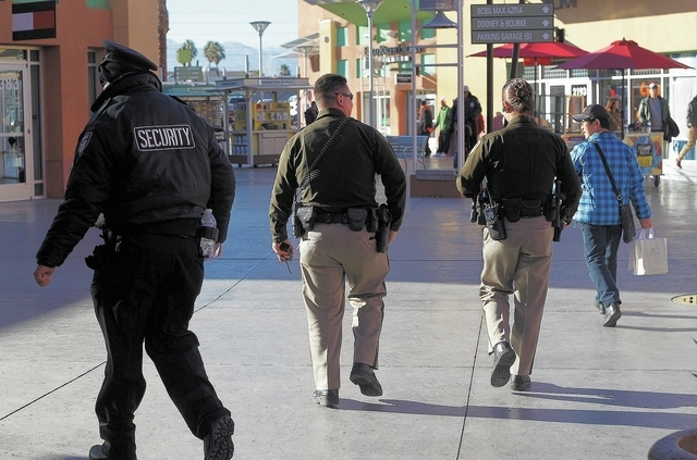 Metro Police officers and a mall security officer walk the grounds of the Las Vegas Premium Outlets near downtown Las Vegas on Dec. 10, 2013. (Jason Bean/Las Vegas Review-Journal)