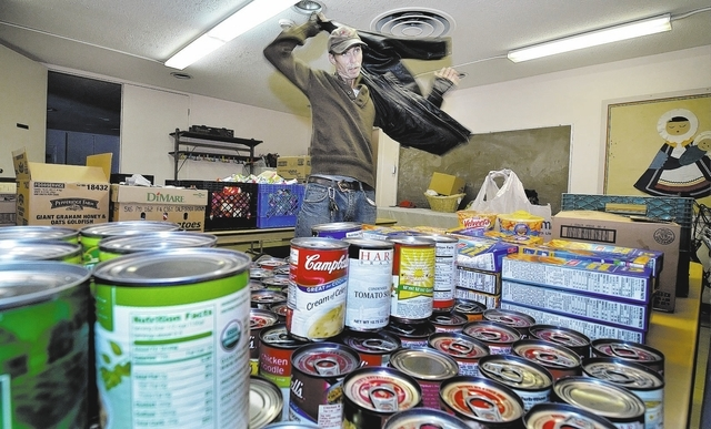 Homeless Marine veteran Michael Coughlin puts on his jacket in the food pantry at the Westminster Presbyterian Church at 4601 W. Lake Mead Blvd. in Las Vegas Friday, Dec. 13, 2013. Coughlin, who's ...