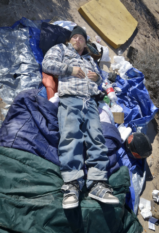 Byron Johnson lies in his makeshift bed at a homeless encampment near Lake Mead Boulevard and North Simmons Street in Las Vegas Friday, Dec. 13, 2013. Johnson is one of the people being helped by  ...