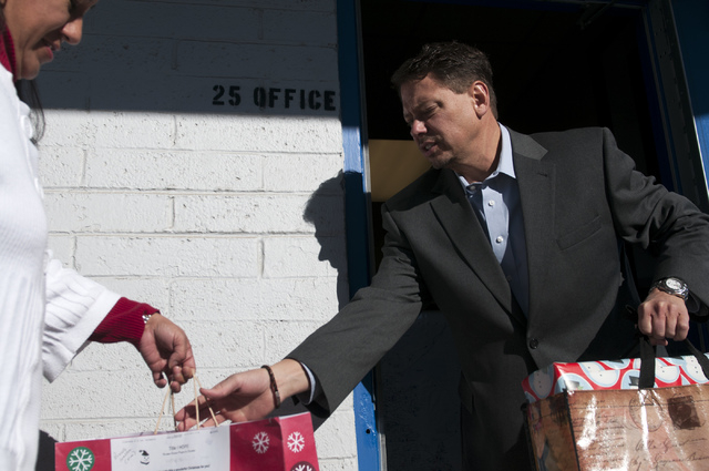 Estela Daley, left, secretary at Title 1 Homeless Outreach Program For Education, hands over wrapped gifts to Pat Skorkowsky, Clark County School District superintendent, during his visit to Title ...
