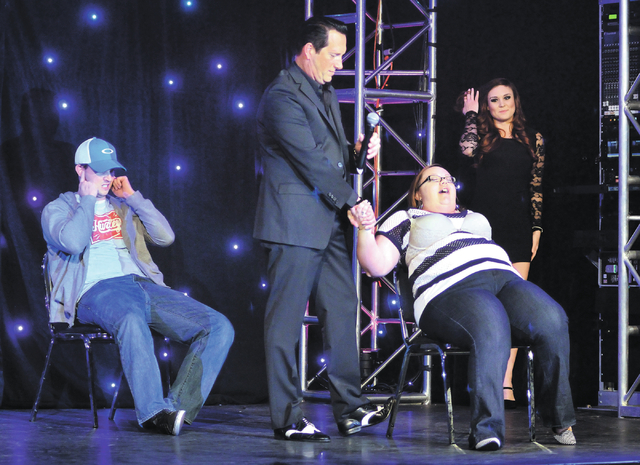 Hypnotist Anthony Cools, center, has a moment with an audience member as assistant Kristina Corey, right, watches and another audience member, left, tries to keep from hearing the proceedings duri ...