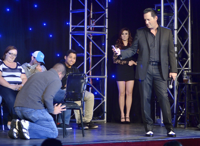 "Hypnotist Anthony Cools, right, takes a shot of an audience member in a compromising position during the ""Anthony Cools Experience"" in the Paris hotel-casino at 3655 Las Vegas Blvd., Sou ..."