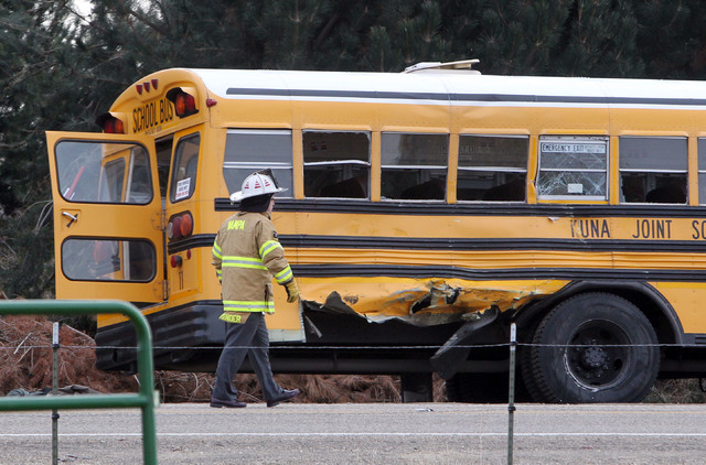A firefighter walks past the damaged Kuna School District bus at the scene of a fatal crash on Thursday in Kuna, Idaho. Authorities said one child died and five people were injured, including four ...