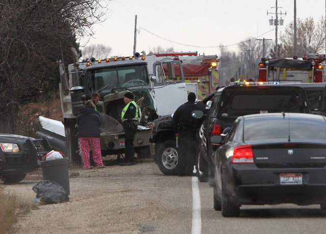 Law enforcement officials respond to the scene of a fatal crash on Thursday in Kuna, Idaho. Authorities say one child has died and five people were injured, including four children, when a dump tr ...