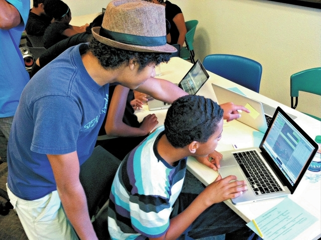 Teenagers use a Mac laptop to edit a multimedia collaboration during a three-day TechArt Studio workshop at the West Las Vegas Library in June. (Photo courtesy of the Las Vegas-Clark County Librar ...
