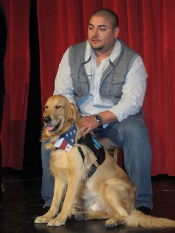 Tony Ray Silva pets Freedom at a passing of the leash ceremony Dec. 10 at the Sun City Anthem Center. Clubs in Sun City Anthem raised $1,500 to get Silva, an Iraqi-war veteran, a service dog. (Spe ...