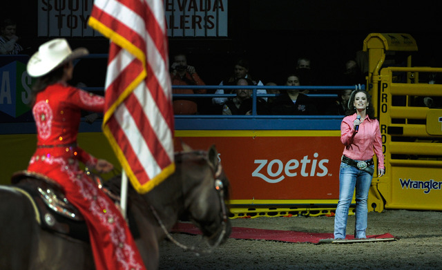 Television host Jackie Schmillen of Des Moines, Iowa, sings the national anthem before the start of the fourth round at the 55th Wranglers National Finals Rodeo at the Thomas & Mack Center on Sund ...
