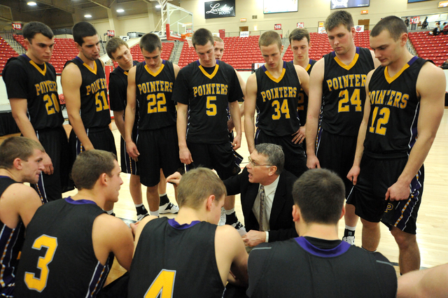 University of Wisconsin Stevens Point head coach, Bob Semling, bottom center in the suit and tie, coaches his team during their game played against Whitworth University at the D3hoops.com Classic  ...