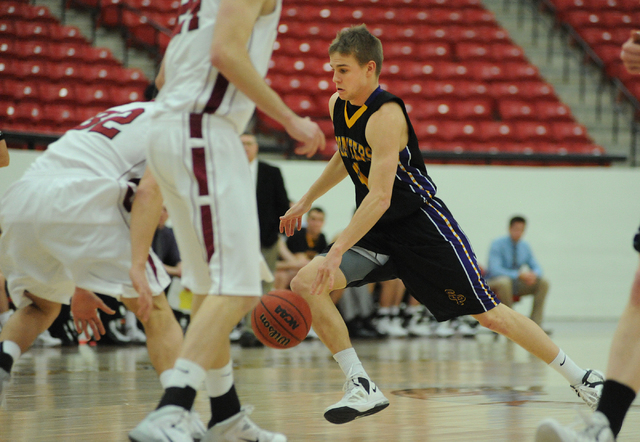 University of Wisconsin Stevens Point basketball player Tyler Tillema (4), center, dribbles the basketball against George Valle (32) of Whitworth University during the D3hoops.com Classic at the S ...