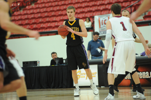 University of Wisconsin Stevens Point basketball player Tyler Tillema (4), center, surveys the defense against Robby Douglas (1) of Whitworth University during the D3hoops.com Classic at the South ...