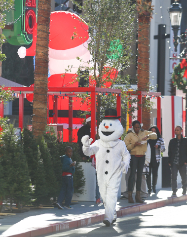 Shane Ross as Frosty the Snowman walks around at the Jingle Bell Block event on Third Street between Stewart and Ogden avenues. (Chase Stevens/Las Vegas Review-Journal)