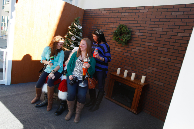 From left, Kendra Meyers, Kati Welt and Kim Mamer sit for a photo with Glenn Rodgers as Santa Claus at the Jingle Bell Block event on Third Street between Stewart and Ogden avenues. (Chase Stevens ...
