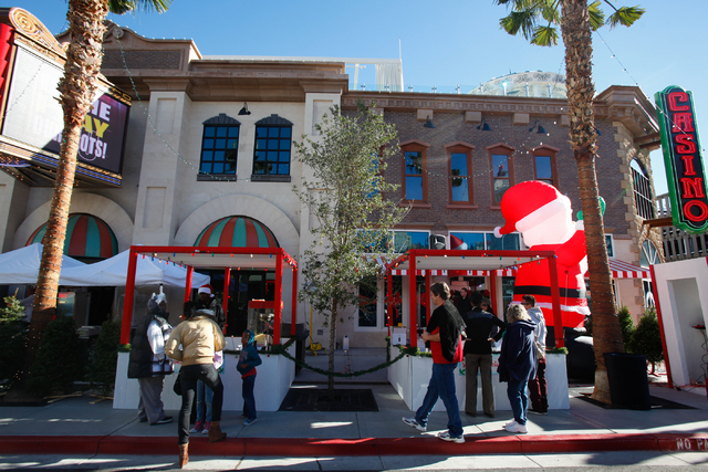 People walk around at the Jingle Bell Block event on Thirrd Street between Stewart and Ogden avenues on Saturday. The event, held by Downtown Grand Las Vegas and Downtown3rd, runs through Dec. 24. ...