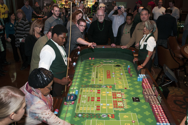 Players gather around a craps table at O'Sheas casino in Las Vegas during their soft opening event Friday, Dec. 27, 2013 (Erik Verduzco/Las Vegas Review-Journal)