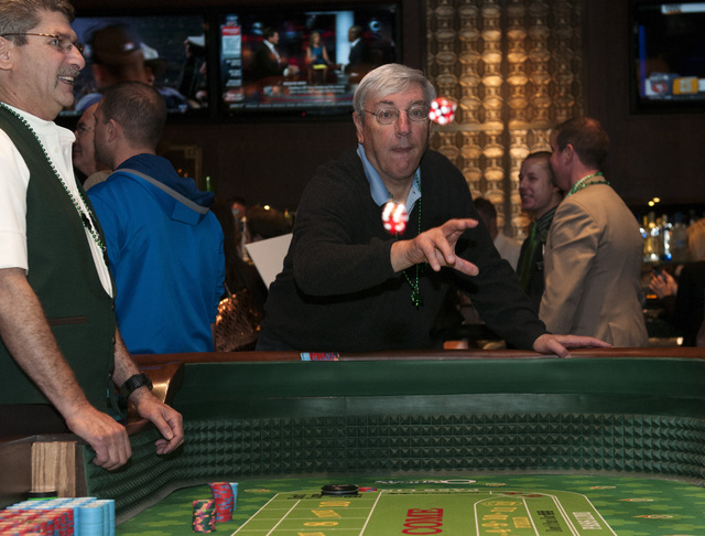 Ron Bossi rolls a pair of dice during a game of craps at O'Sheas casino in Las Vegas during their soft opening event on Friday, Dec. 27, 2013. (Erik Verduzco/Las Vegas Review-Journal)
