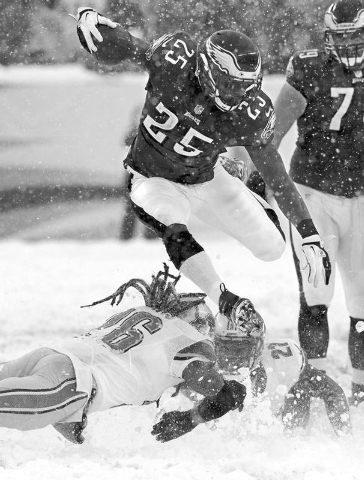 Philadelphia Eagles' LeSean McCoy (25) leaps over two would-be Detroit Lions tacklers as he runs to score his first of two touchdowns of an NFL football game on Sunday, Dec. 8, 2013, in Philadelph ...