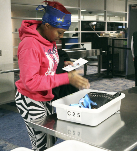 Alexis Boothe, of Chicago, drops her personal items in a bin in the TSA screening line at McCarran International Airport in Las Vegas, Dec. 3, 2013. More than $500,000 was found last year in loose ...
