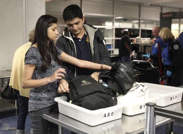Ankita and Rohit Jain, left to right, of Denver, sort through their personal items in the TSA screening line at McCarran International Airport in Las Vegas, Dec. 3, 2013. More than $500,000 was fo ...