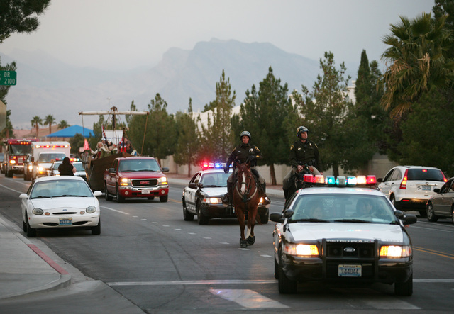 Las Vegas Metropolitan Police Department mounted unit Officer Kelly Korb, center, and Officer Tom Ruiz ride in a parade along Balzar Avenue near North Torrey Pines Drive Thursday.  Officers from t ...