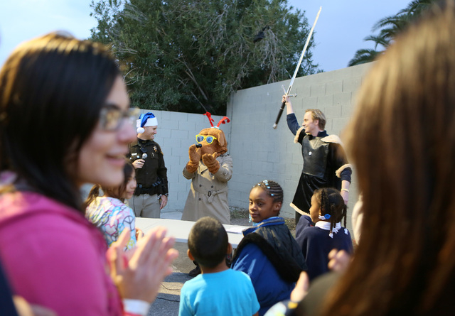 Las Vegas Metropolitan Police Department Officer Josh Stark, left, McGruff the Crime Dog and Christian Schoyen, right, cheer during a neighborhood block party Thursday.  Officers from the LVMPD No ...