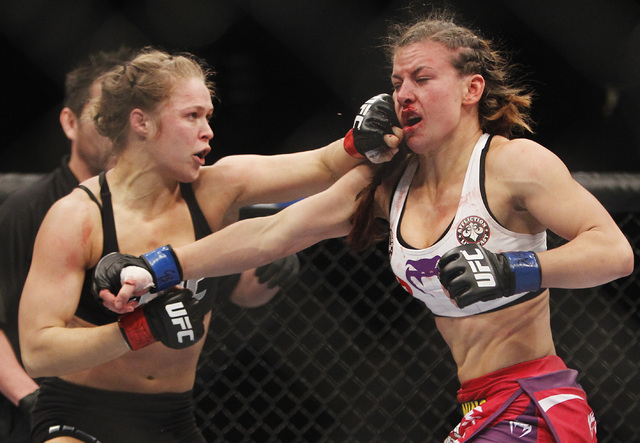 Ronda Rousey, left, hits Miesha Tate during UFC 168 at the MGM Grand Garden Arena in Las Vegas on Friday, Dec. 28, 2013. (Jason Bean/Las Vegas Review-Journal)