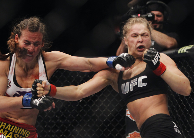 Miesha Tate, left, hits Ronda Rousey during UFC 168 at the MGM Grand Garden Arena in Las Vegas on Friday, Dec. 28, 2013. (Jason Bean/Las Vegas Review-Journal)