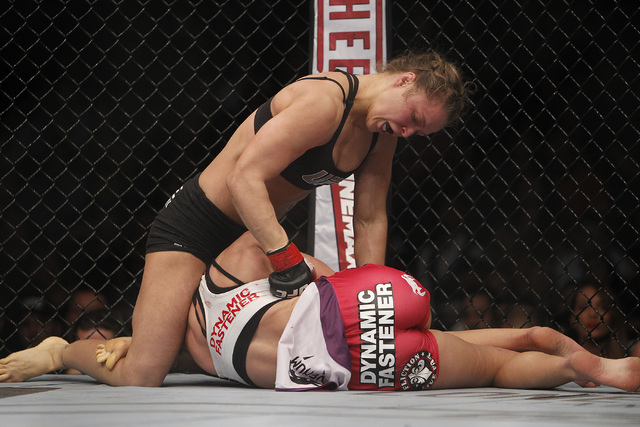 Ronda Rousey, top, hits Miesha Tate during UFC 168 at the MGM Grand Garden Arena in Las Vegas on Friday, Dec. 28, 2013. (Jason Bean/Las Vegas Review-Journal)
