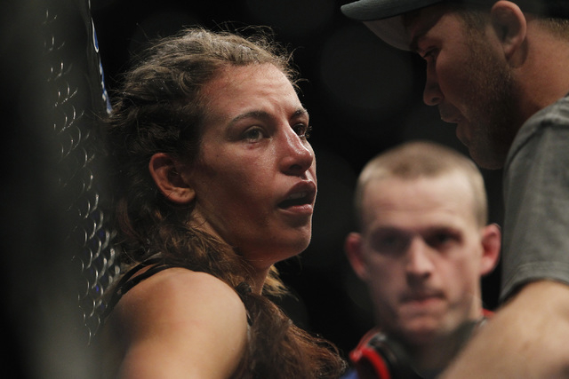 Miesha Tate gathers herself after losing to Ronda Rousey during UFC 168 at the MGM Grand Garden Arena in Las Vegas on Friday, Dec. 28, 2013. (Jason Bean/Las Vegas Review-Journal)