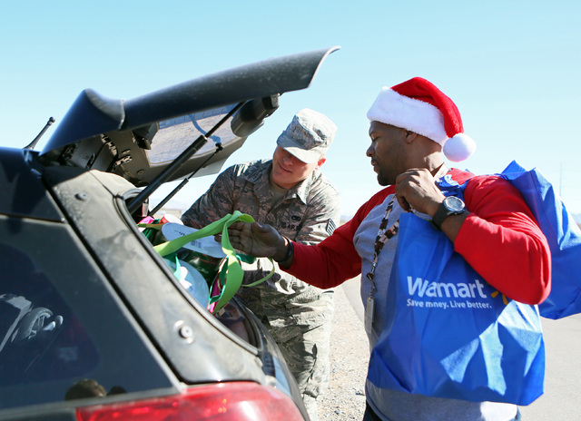"""U.S. Air Force Staff Sgt. James Hardy, center, helps volunteer Kevin """"Q"""" Qualls put bags of groceries into Hardy's car during an Operation Homefront """"Holiday Meals for Military"""" event at ..."""
