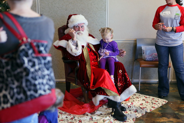 """Santa Claus, played by George Cloake, looks over to the mother of Lily Burge, 3, who sits on his lap during a visit at an Operation Homefront """"Holiday Meals for Military"""" event at SkyView YMCA ..."""