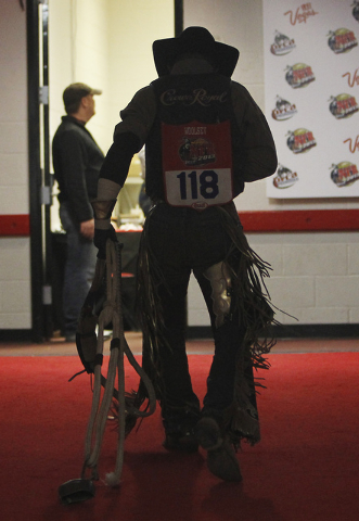 Bull rider Steve Woolsey heads back to the locker room after posting a score of 86.5 during day 1 of the Wrangler National Finals Rodeo at the Thomas and Mack Center in Las Vegas on Dec. 5, 2013.  ...