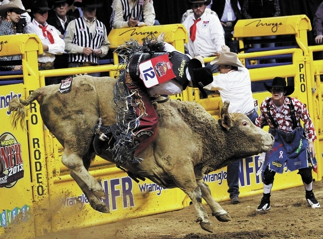 J.W. Harris tries to hold on during the Bull Riding event on day 8 of the Wrangler National Finals Rodeo at the Thomas and Mack Center in Las Vegas on Dec. 12, 2013. (Jason Bean/Las Vegas Review-J ...