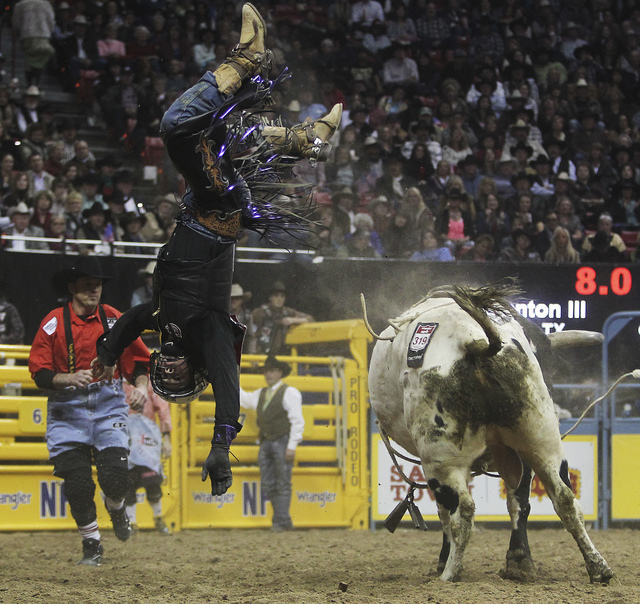 Trey Benton III looks for landing place during round 7 of the Wrangler National Finals Rodeo at the Thomas & Mack Center on Dec. 12, 2012. The 22-year-old bull rider broke his femur earlier this y ...