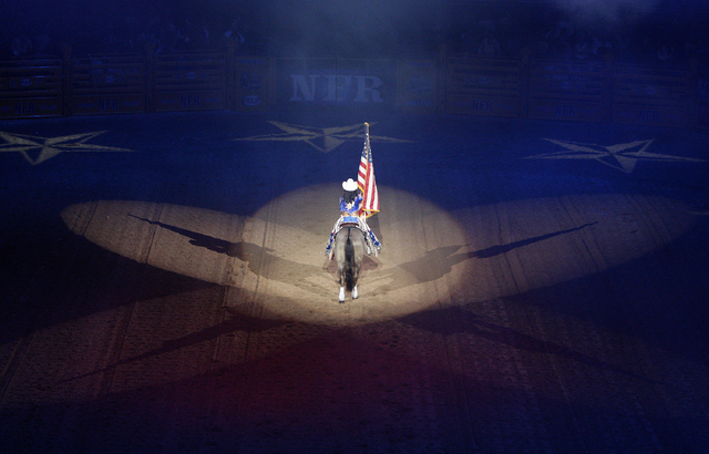 A rider hold up the flag during the opening ceremony on the first night of the National Finals Rodeo at the Thomas & Mack Center in Las Vegas Thursday, Dec. 5, 2013. (John Locher/Las Vegas Review- ...