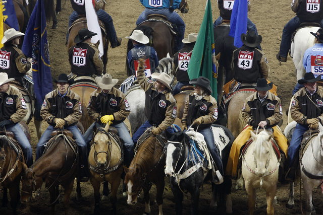 Contestant Shane Slack, center, waives to the crowd during the opening ceremony on the first night of the National Finals Rodeo at the Thomas & Mack Center in Las Vegas Thursday, Dec. 5, 2013. (Jo ...