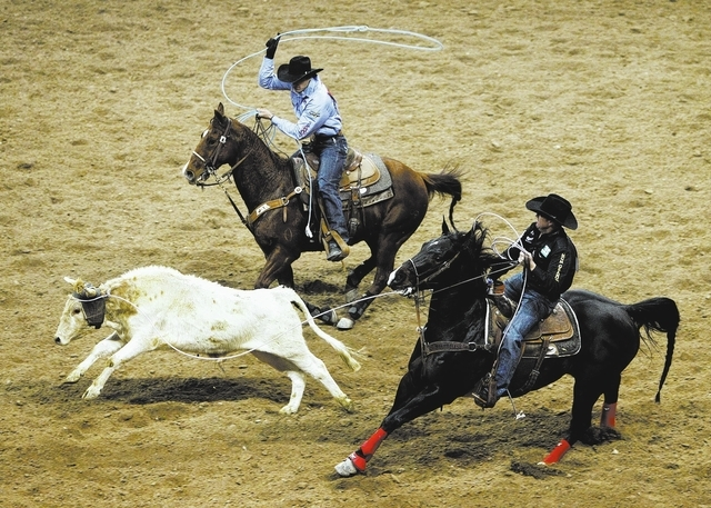 Trevor Brazile, right, and Patrick Smith compete in the team roping event on the first night of the National Finals Rodeo at the Thomas & Mack Center in Las Vegas Thursday, Dec. 5, 2013. (John Loc ...