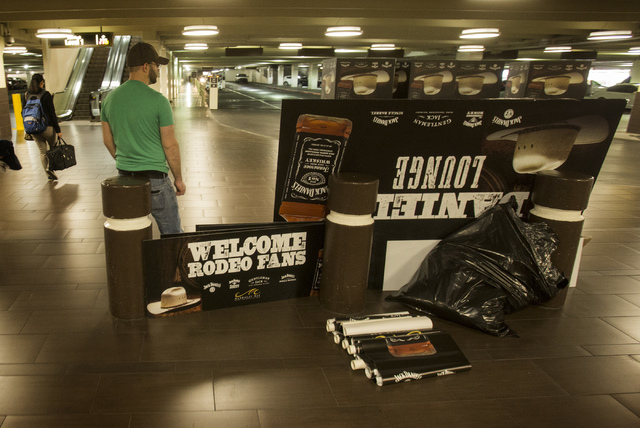 John Donnelly with Envisage Media Solutions stands beside signs inside the Mandalay Bay parking garage on Monday, Dec. 16, 2013. His company did the signs for a Jack Daniels event at the resort du ...