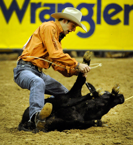 Shane Hanchey ties down his calf during the fourth round at the 55th Wranglers National Finals Rodeo at the Thomas & Mack Center on Sunday. Hanchey had a score of 8.6 second to finish sixth in the ...