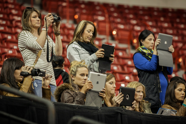 Women take video during the National Finals Rodeo team roping practice at Thomas & Mack Center on Tuesday. The contestants will analyze the video of their ride and how the steer moves. (Jeff Schei ...