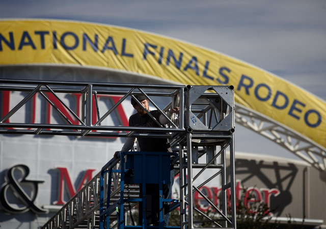 John Hollingsted works on the stage at the Wrangler NFR Pro Rodeo in front of the Thomas & Mack Center on Tuesday in preparation of the 10-day National Finals Rodeo, which kicks off Thursday. (Jef ...