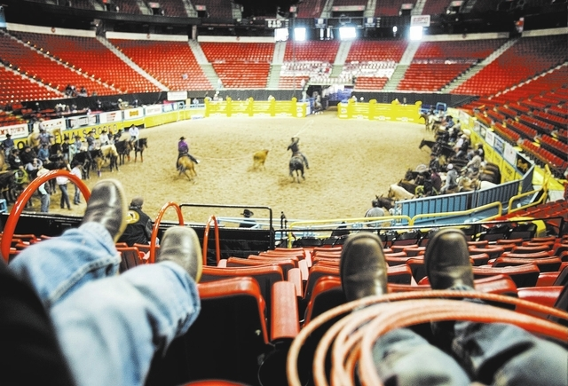 Jace Davis,left, and Braylon Tryan, both 5, watch National Finals Rodeo team ropers practice at Thomas and Mack  Arena on Tuesday, Dec. 3, 2013. There fathers Justin Davis and Chase Tryan are comp ...