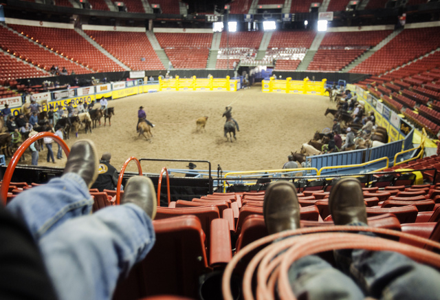 Jace Davis, left, and Braylon Tryan, both 5, watch National Finals Rodeo team ropers practice at the Thomas & Mack Center on Tuesday. Their fathers, Justin Davis and Chase Tryan, are competing in  ...